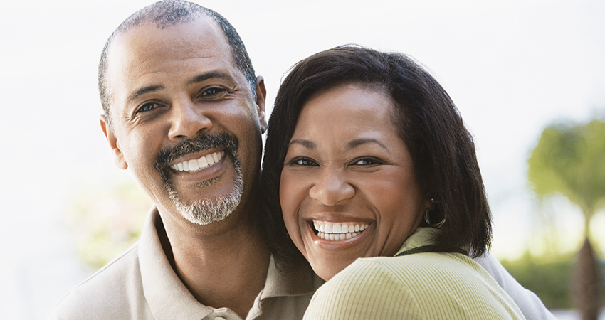 black couple 50s 60s smiling cuddling looking into camera